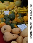 Small photo of Heap of multicolored, striped Carnival Squash, Butternut Squash and Acorn Squash for sale at the outdoor, organic farmers' market in Palm Springs, California.