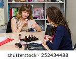 Small photo of Beauty consultant monitors the client, coloring lips