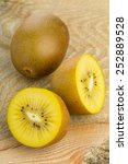 Small photo of Whole and cut golden kiwifruit/ kiwi (Actinidia chinensis) on wooden cutting board