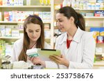 two young female pharmacist in... | Shutterstock . vector #253758676