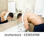 Attractive Man Washing Face In...