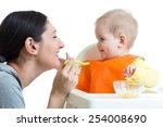Mother Feeding Baby Girl With...