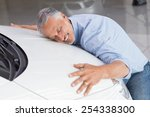 Stock photo smiling man hugging a white car at new car showroom 254338300