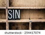 "Small photo of The word ""SIN"" written in vintage metal letterpress type in a wooden drawer with dividers."