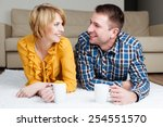Happy young couple at home drinking tea - stock photo