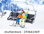 Mother With Boy Lifting On Ski...