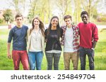 Small photo of Multiethnic group of teenagers outdoor. They are embraced at park, two boys and one girl are caucasian, one boy and one girl are black. Friendship, immigration, integration and multicultural concepts.