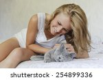 Stock photo young beautiful woman with british cat on the bed 254899336
