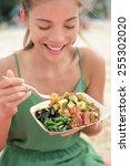 Small photo of Woman eating local Hawaii food dish Poke bowl salad. Girl enjoying healthy lunch - a traditional local Hawaiian dish with raw marinated ahi yellowfin tuna fish. Healthy lifestyle concept.