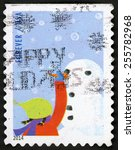 Small photo of UNITED STATES OF AMERICA - CIRCA 2014: forever Christmas post stamp printed in USA shows little girl in red jacket building snowman; affixing carrot nose; winter fun, circa 2014