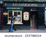 Small photo of KILLARNEY, IRELAND - 14TH FEBRUARY 2015: A man and child walk past O'conners traditional Irish pub in the town of Killarney, Killarney is well known for its traditional Irish pubs.