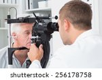 Male optician examining senior...