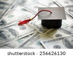 Small photo of Graduation mortar board cap on one hundred dollar bills concept for the cost of a college and university education