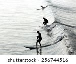 Three Silhouettes Of Surfers In ...