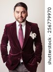 Small photo of Elegant young handsome man in luxury velvet claret costume. Studio fashion portrait.