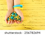hands with blue yellow candies  ... | Shutterstock . vector #256782694