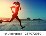 Stock photo young healthy lifestyle woman running at sunrise beach 257072050