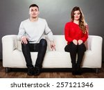 Stock photo shy woman and man guy sitting near attractive young woman on sofa and making hand gesture walking 257121346
