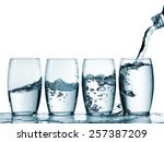 Water Pouring Into Four Glasses
