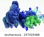 Small photo of Color drop in water, photographed in motion. Ink swirling in water. Cloud of silky ink in water isolated on white background. Colorful ink in water, ink drop. Action painting.