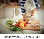 young woman cutting vegetables... | Shutterstock . vector #257589130