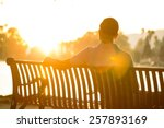 Small photo of A man is sitting on a bench pondering life during a dramatic, warm sunset.