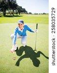 smiling lady golfer kneeling on ... | Shutterstock . vector #258035729