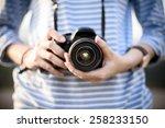 hipster girl holds  camera in... | Shutterstock . vector #258233150