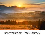 Stock photo sunrise mountain village in the fog and everything nice in yellow light 258350999