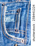 Small photo of blue jeans texture - furl folded grunge fiber torn clothes closeup background