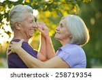 Small photo of Happy Mature couple dancing in autumn park on sunset