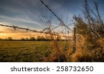A Barbed Wire Fence With Woode...