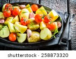 Potato with rosemary and garlic ready to grill - stock photo