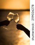 raising a glass in the sunset   Shutterstock . vector #259026278
