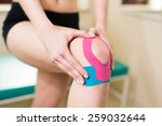 Woman Massages Injured Knee...