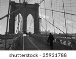 A black and white of people crossing the Brooklyn Bridge on a cold Winters day. - stock photo