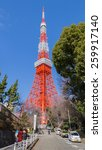 Small photo of Tokyo - January 28, 2015: Television red high tower against the blue sky and the adjoining street with people and cars January 28, 2015, Tokyo, Japan