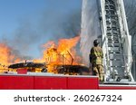 Small photo of A fireman standing at the controls of an 105 foot reach aerial ladder/truck directs a stream of water on a blazing building.