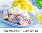 Stock photo herring with onion on blue plate 260452013