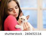 Stock photo portrait of a beautiful brunette holding a cute kitten 260652116