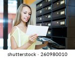 Small photo of Smiling blonde girl taking junk mail out the posting box