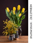 Small photo of Two spring yellow bouquet of flowers in vintage pots on dark background. Tulips and mimosa (Acacia dealbata).
