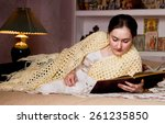 Stock photo russian woman reading with her cat in bed room 261235850