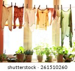 Stock photo baby laundry hanging on a clothesline with sun rising on a background 261510260