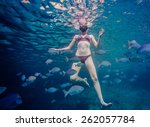 Small photo of Girl Snorkeling in the Ocean and Surrounded with Chopa Fishes