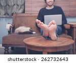 Stock photo a happy barefoot man is resting his feet on a coffee table at home while working on his laptop 262732643