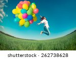 Small photo of Happy girl jumping with colorful toy balloons outdoors. Young woman having fun in green spring field against blue sky background. Freedom concept