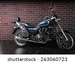 Full Length Profile of Blue Standard Cruiser Style Motorcycle in front of Brick Wall - stock photo