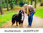 Stock photo woman and dog at retrieving stick game in fall park on dirt path 263099159