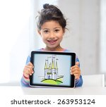 Small photo of technology, childhood, entertainment, fairytale and imagination concept - happy little girl showing picture of castle on tablet pc computer screen at home